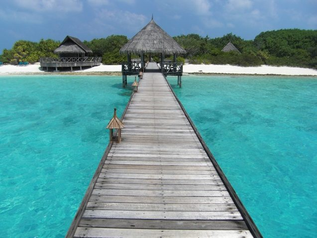 Dock and thatched roof huts in the Maldives.